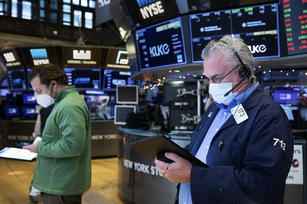 In this photo provided by the New York Stock Exchange, Frank O.Connell, right works with a feel trader on the floor, Tuesday, Jan. 12, 2021. (Colin Ziemer/New York Stock Exchange via AP)