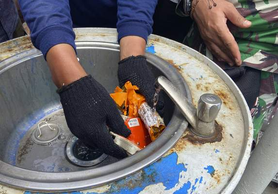 Indonesian navy personnel inspect a part the flight data recorder recovered at the crash site of the Sriwijaya Air flight SJ-182 at the Tanjung Priok Port, Tuesday, Jan. 12, 2021. (AP Photo/Fadlan Syam)