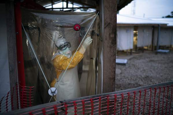 FILE - In this Saturday, July 13, 2019, file photo, a health worker wearing protective suit enters an isolation pod to treat a patient at a treatment center in Beni, Congo DRC. (AP Photo/Jerome Delay, File)