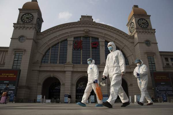 FILE - In this April 7, 2020, file photo, workers in protective suits walk past the Hankou railway station on the eve of its resuming outbound traffic in Wuhan in central China's Hubei province. (AP Photo/Ng Han Guan, File)