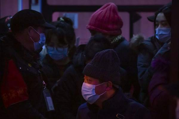 People wearing face masks to protect against the spread of the coronavirus stand on a public bus in the central business district in Beijing, Tuesday, Jan. 12, 2021. (AP Photo/Mark Schiefelbein)
