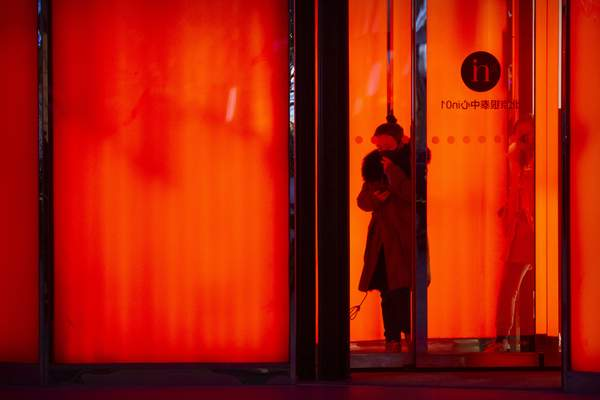 A woman wearing a face mask to protect against the spread of the coronavirus walks out of a shopping mall in the central business district in Beijing, Tuesday, Jan. 12, 2021. (AP Photo/Mark Schiefelbein)