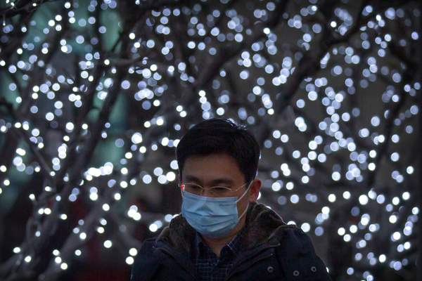 A man wearing a face mask to protect against the spread of the coronavirus walks past a light display in the central business district in Beijing, Tuesday, Jan. 12, 2021. (AP Photo/Mark Schiefelbein)