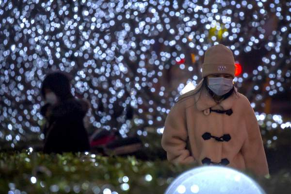 People wearing face masks to protect against the spread of the coronavirus walk past a light display in the central business district in Beijing, Tuesday, Jan. 12, 2021. (AP Photo/Mark Schiefelbein)