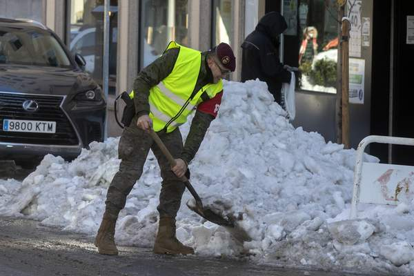 A military police officer clears snow and ice from the street in Madrid, Spain, Tuesday, Jan. 12, 2021. (AP Photo/Paul White)