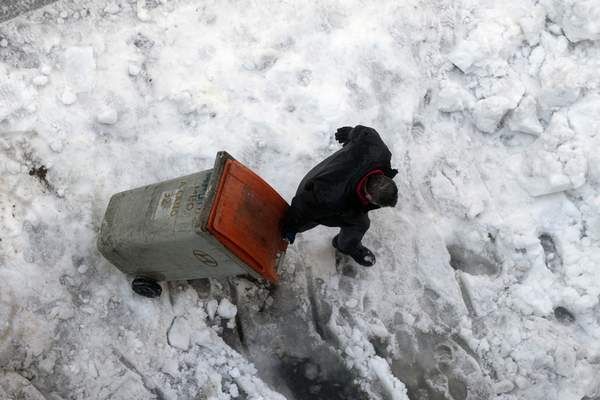 A man drags a garbage container through snow and ice in Madrid, Spain, Monday, Jan. 11, 2021. (AP Photo/Paul White)
