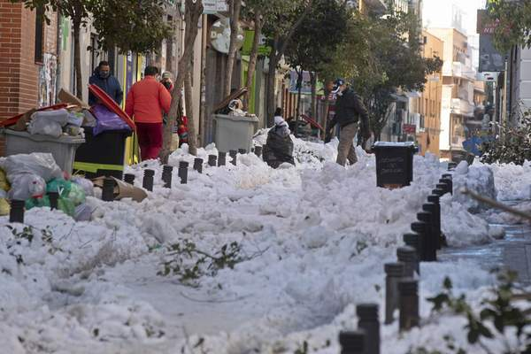 A man walks across a street covered with snow and ice in Madrid, Spain, Tuesday, Jan. 12, 2021. (AP Photo/Paul White)