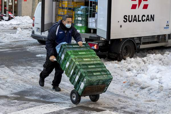 A worker wheels a food delivery trolley in the snow and ice in Madrid, Spain, Tuesday, Jan. 12, 2021. (AP Photo/Paul White)