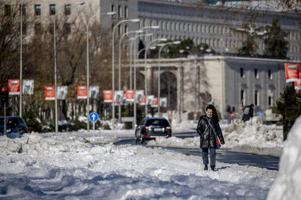 A woman walks along Paseo Castellana covered with the snow in Madrid, Spain, Monday, Jan. 11, 2021. (AP Photo/Manu Fernandez)