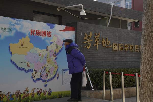 An elderly Chinese man looks at map of Chinese showing its different ethnic groups and the slogan Ethnic Unity in Beijing, China Monday, Jan. 11, 2021. (AP Photo/Ng Han Guan)