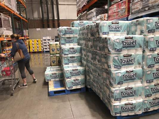 A shopper loads her basket next to a display of paper towels in a Costco warehouse in this photograph taken Wednesday, Nov. 18, 2020, in Sheridan, Colo. (AP Photo/David Zalubowski)