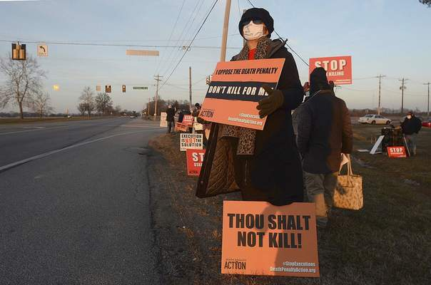 Karen Burkhart holds a sign across the road from the Federal Correctional Complex in Terre Haute, Ind., to protest the scheduled execution of Lisa Montgomery, Tuesday, Jan. 12, 2021. (Joseph C. Garza/The Tribune-Star via AP)