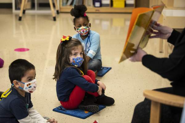 Associated Press Pre-kindergarten students listen as their teacher reads a story Monday at Dawes Elementary in Chicago.