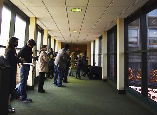 An audience watches from inside the walkway as the new marquees are turned on. The marquees are the highest-resolution outdoor signs in the state. The previous marquees were installed 17 years ago.