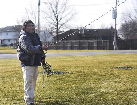 Katie Fyfe | The Journal Gazette Marvin Flores, with Lawnscape Land Management, takes down Christmas decorations Wednesday at the entrance of the Cherry Hill neighborhood.