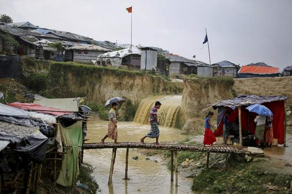 FILE - In this Aug. 28, 2018, file photo, sewer water flows in the back as Rohingya refugees cross a makeshift bamboo bridge at Kutupalong refugee camp, Bangladesh. (AP Photo/Altaf Qadri, File)
