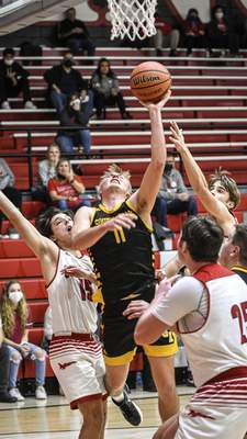 Mike Moore | The Journal Gazette South Adams senior James Arnold scores under the basket while being fouled in the second period against Adams Central on Friday.