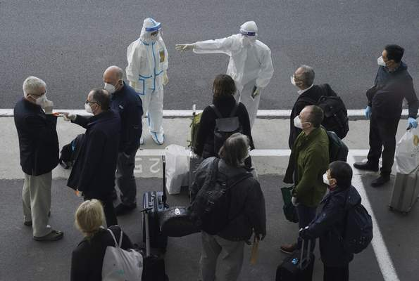 Associated Press A worker in protective coverings directs members of the World Health Organization team on their arrival Thursday at the airport in Wuhan, China.