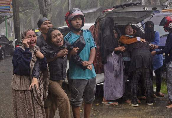 People react as the body of a relative is retrieved from the ruin of a building at an area affected by an earthquake in Mamuju, West Sulawesi, Indonesia, Friday, Jan. 15, 2021. (AP Photo/Yusuf Wahil)
