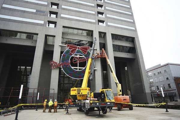 Katie Fyfe | The Journal Gazette  Workers take down the Merry Christmas wreath at the Indiana Michigan Power building Thursday afternoon.