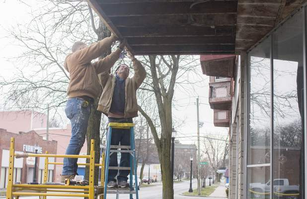 Michelle Davies | The Journal Gazette  Andrew Faux, left, and Chris Dennison, right, both with American Renovations, work on repairing the soffit of a store along Fairfield Avenue Thursday morning.