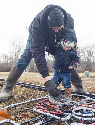 Michelle Davies | The Journal Gazette  Ryne Walter, 2, helps his dad, Andy Walter with Blue Jacket, as he dismantles a light display at Fantasy of Lights Friday at Franke Park.