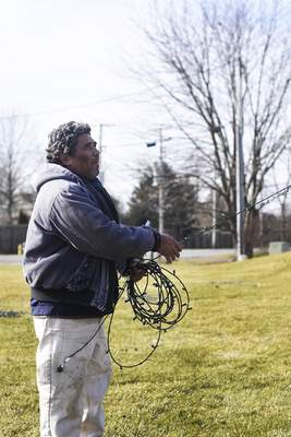 Katie Fyfe | The Journal Gazette  Marvin Flores takes down Christmas decorations at the Cherry Hill entrance Wednesday afternoon.
