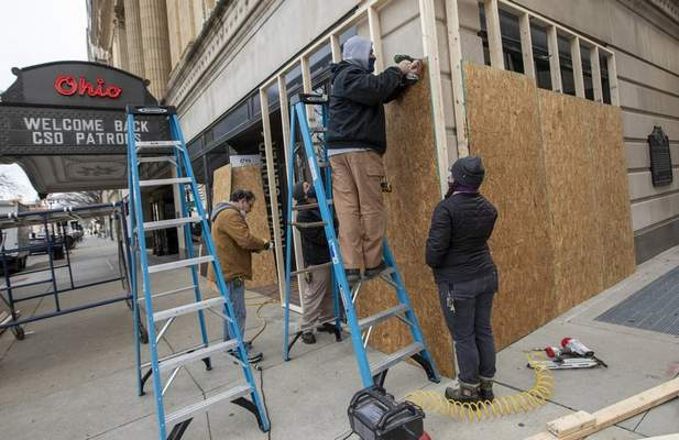 Stagehands from the Ohio Theatre board up the building's windows in preparation for planned weekend protests in Columbus on Thursday, Jan. 14, 2021. (Adam Cairns/The Columbus Dispatch via AP)