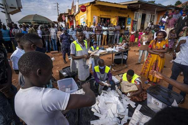 Election officials count the ballots after polls closed in Kampala, Uganda, Thursday, Jan. 14, 2021.Ugandans voted in a presidential election tainted by widespread violence that some fear could escalate as security forces try to stop supporters of leading opposition challenger Bobi Wine from monitoring polling stations. (AP Photo/Jerome Delay)