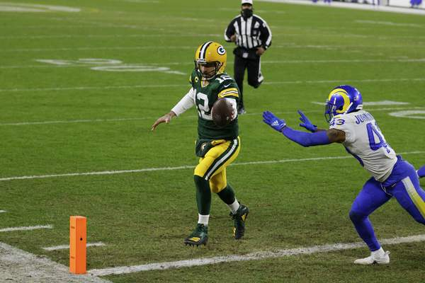 Green Bay Packers quarterback Aaron Rodgers scores on a one-yard touchdown run past Los Angeles Rams' John Johnson during the first half of an NFL divisional playoff football game, Saturday, Jan. 16, 2021, in Green Bay, Wis. (AP Photo/Matt Ludtke)