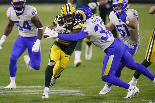 Green Bay Packers' Aaron Jones (33) is tackled by Los Angeles Rams' Jordan Fuller (32) during the first half of an NFL divisional playoff football game Saturday, Jan. 16, 2021, in Green Bay, Wis. (AP Photo/Matt Ludtke)