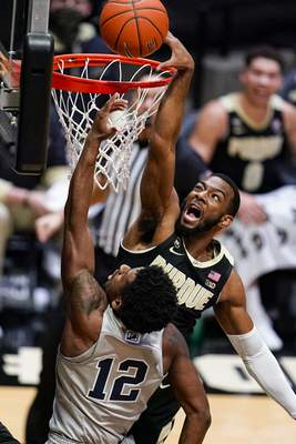 Purdue forward Aaron Wheeler, top, blocks the shot of Penn State guard Izaiah Brockington (12) during the first half of an NCAA college basketball game in West Lafayette, Ind., Sunday, Jan. 17, 2021. (AP Photo/Michael Conroy)