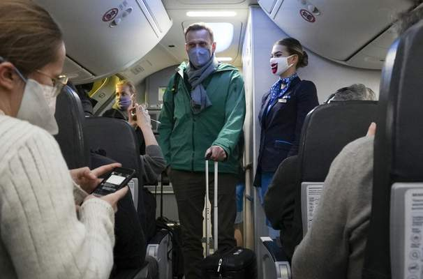Alexei Navalny and his wife Yulia board the plane prior to flight to Moscow in the Airport Berlin Brandenburg (BER) in Schoenefeld, near Berlin, Germany, Sunday, Jan. 17, 2021. (AP Photo/Mstyslav Chernov)