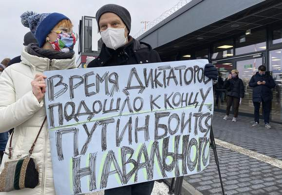 Navalny supporters hold a poster reading 'The time of dictators has come to the end. Putin is afraid of Navalny', outside of the Terminal 5 of the Airport Berlin Brandenburg (BER) in Schoenefeld, near Berlin, Germany, Sunday, Jan. 17, 2021. (AP Photo/Mstyslav Chernov)