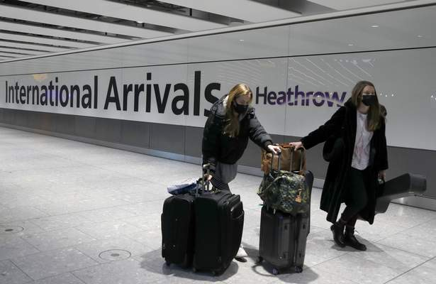 Travellers arrive at Heathrow Airport in London, Sunday, Jan. 17, 2021. (AP Photo/Frank Augstein)