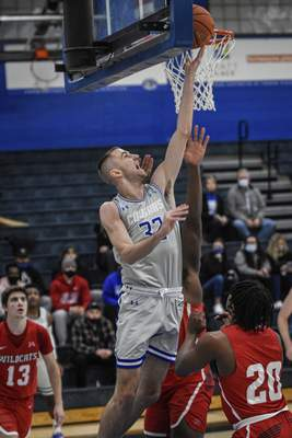 Mike Moore | The Journal Gazette Saint Francis forward Jeff Reynolds scores under the basket in the first half against Indiana Wesleyan University at the Hutzell Athletic Center on Monday
