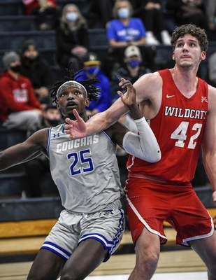 Mike Moore | The Journal Gazette Saint Francis forward David Ejah, left and Indiana Wesleyan center Seth Maxwell watch for a rebound in the first half at the Hutzell Athletic Center on Monday.