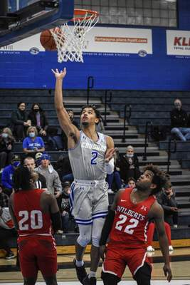 Mike Moore | The Journal Gazette Saint Francis guard Jalan Mull scores under the basket in the first half against Indiana Wesleyan University at the Hutzell Athletic Center on Monday.