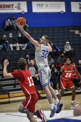 Mike Moore | The Journal Gazette Saint Francis forward Jeff Reynolds catches a high pass on Monday in the first half against Indiana Wesleyan University at the Hutzell Athletic Center.