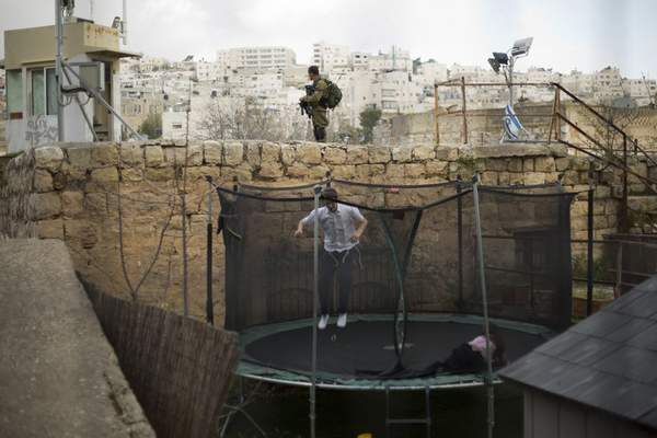 FILE - In this March 7, 2019, file photo, settlers jump on a trampoline as an Israeli solider stands guard in the Israeli controlled part of the West Bank city of Hebron. (AP Photo/Ariel Schalit, File)