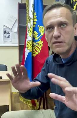 In this image taken from video released by Kira Yarmysh on her Twitter account, Russian opposition leader Alexei Navalny gestures as he waits for a court hearing in a police station in Khimki, outside in Moscow, Russia, Monday, Jan. 18, 2021. (@Kira_Yarmysh via AP)