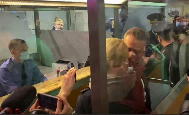 In this photo taken from video, Alexei Navalny kisses his wife Yulia as he is detained by police at the passport control after arriving at Sheremetyevo airport, outside Moscow, Russia, Sunday, Jan. 17, 2021. (AP)