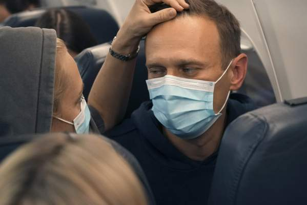 Alexei Navalny and his wife Yulia sit on the plane on a flight to Moscow, at the Airport Berlin Brandenburg (BER) in Schoenefeld, near Berlin, Germany, Sunday, Jan. 17, 2021. (AP Photo/Mstyslav Chernov)