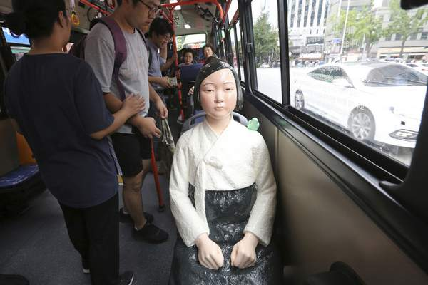 FILE - In this Aug. 14, 2017, file photo, a comfort woman statue is placed on a chair of a bus to mark the 5th International Memorial Day for Comfort Women, in Seoul, South Korea. (AP Photo/Ahn Young-Joon, File)