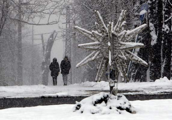 A couple walk along a snow covered path in Belgrade, Serbia, Sunday, Jan. 17, 2021. Meteorologists predict sub zero temperatures in Serbia throughout the coming week. (AP Photo/Darko Vojinovic)