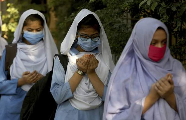 Students wearing face masks to prevent the spread of the coronavirus as they pray upon their arrival at their school, in Karachi, Pakistan, Monday, Jan. 18, 2021. (AP Photo/Fareed Khan)