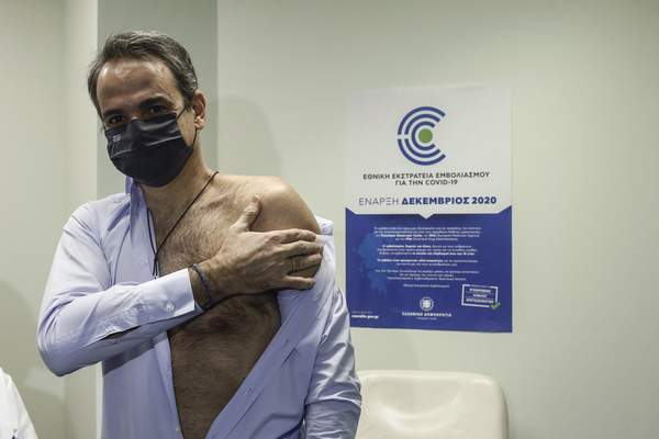 Greek Prime Minister Kyriakos Mitsotakis holds his arm after receiving a shot of the second dose of the Pfizer-BioNTech vaccine against the COVID-19 virus, at the Attikon University Hospital in Athens, Greece, on Monday Jan. 18, 2021. (Yannis Kolesidis/Pool via AP)