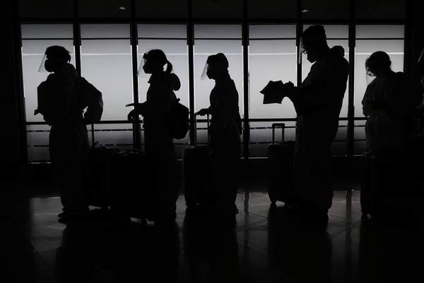 Foreign passengers wearing protective suits prepare for their flight to China at Manila's International Airport, Philippines, Monday, Jan. 18, 2021. (AP Photo/Aaron Favila)