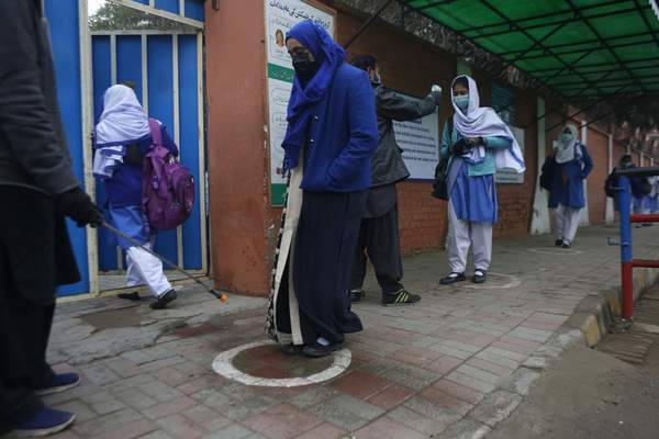 A worker sprays sanitizer on the shoes of students wearing face masks to prevent the spread of the coronavirus as they arrive at their school, in Lahore, Pakistan, Monday, Jan. 18, 2021. (AP Photo/K.M.Chaudary)