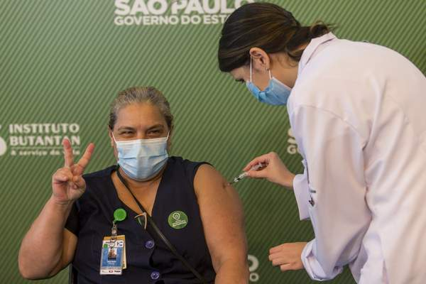 A woman celebrates as she gets her shot of the COVID-19 vaccine produced by China's Sinovac Biotech Ltd, at the Hospital das Clinicas in Sao Paulo, Brazil, Sunday, Jan. 17, 2021. (AP Photo/Carla Carniel)